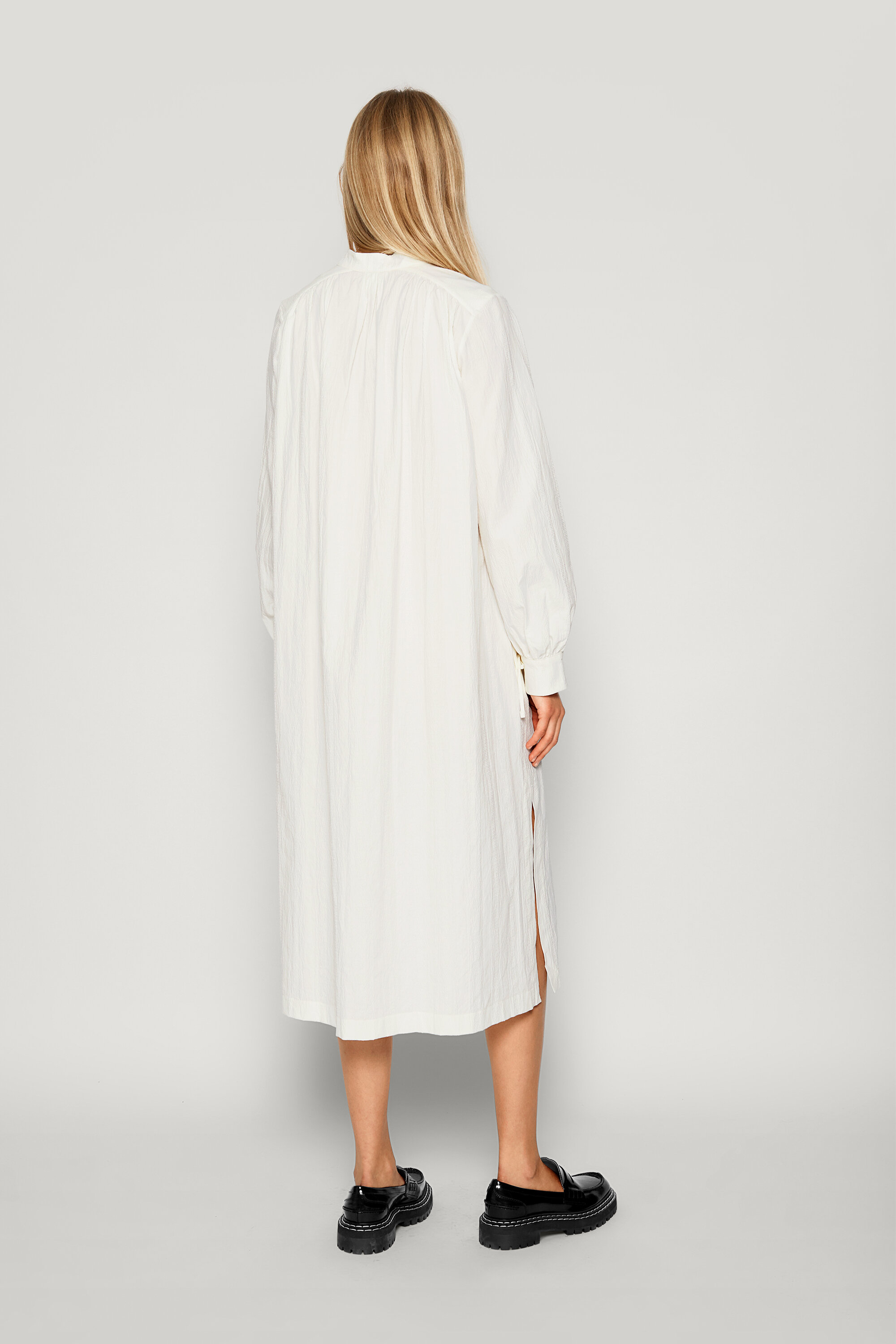 Aradia Dress Cloud Dancer This textured, semi-structured midi-length cotton dress has an open neck with a tie at the top - detail image