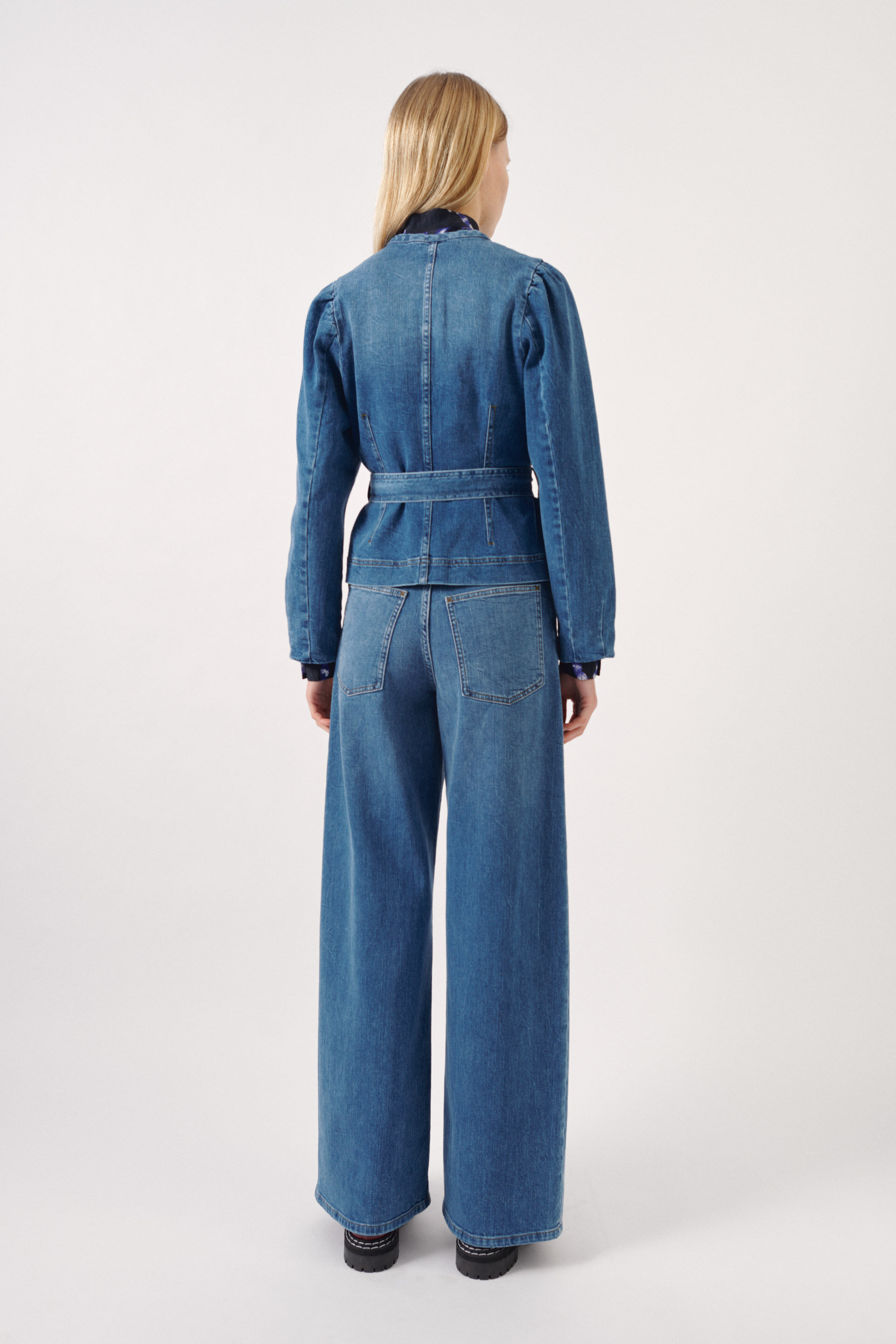 Balzak Jacket Blue Washed Denim This structured denim jacket features button closures down the front, gently puffed shoulders, and a tie belt at the waist - detail image